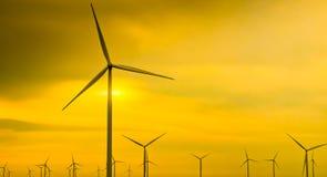 在金黄天空背景的风轮机 免版税库存照片