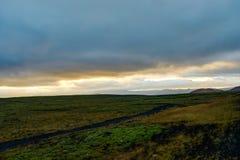 在金黄小时,在冰岛风景的日落与绿色青苔 免版税库存图片