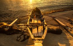 在金黄小时,由海滩的小船 免版税图库摄影