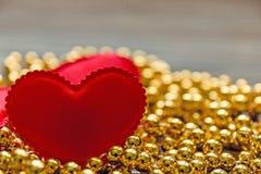 在金黄小珠的红色心脏 图库摄影