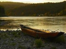 在金黄水背景的小船  免版税库存照片