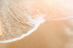 在金黄沙子岸桃红色太阳火光淡色的泡沫似的清楚的海波浪辗压 美好的平静的田园诗风景 海洋海滩 库存照片