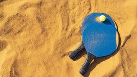 在金黄沙子的球拍和球海滩网球 库存图片