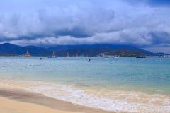 在金黄海滩遥远的旅馆天空云彩的波浪海浪 库存照片