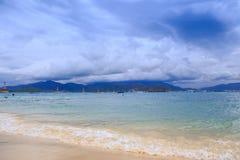 在金黄海滩遥远的游览城市天空云彩的波浪海浪 图库摄影