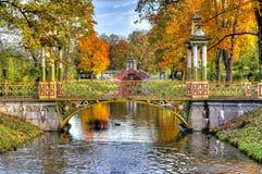 在金黄秋天醇厚的秋天期间的中国桥梁在亚历山大公园,普希金,圣彼得堡,俄罗斯 免版税库存照片