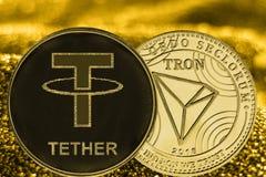在金黄背景的硬币cryptocurrency USDT和TRX 免版税库存照片
