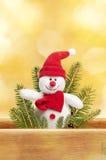 在金黄背景的逗人喜爱的玩具雪人与圣诞老人h 免版税库存照片