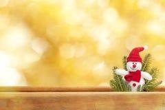 在金黄背景的逗人喜爱的玩具雪人 免版税库存图片