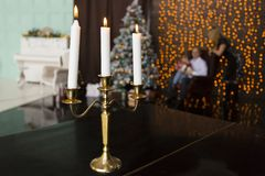 在金黄蜡烛台的三个灼烧的蜡烛在黑桌上在家庭剪影背景中-父母和孩子 免版税图库摄影