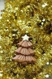 在金黄闪亮金属片的巧克力圣诞树形状 库存图片