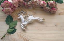 在金黄闪烁的驯鹿与在木背景的俏丽的玫瑰 库存照片