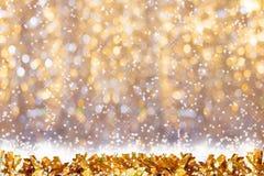 在金黄bokeh背景的金发光的闪亮金属片与雪和拷贝空间的 免版税图库摄影