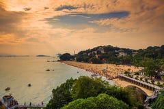 在金黄云彩下的拥挤海滩 免版税库存图片