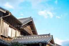 在金黄太阳和早晨蓝色多云天空下的日本传统历史木老房子在日本 图库摄影