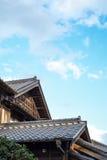 在金黄太阳和早晨蓝色多云天空下的日本传统历史木老房子在日本 库存图片