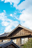在金黄太阳和早晨蓝色多云天空下的日本传统历史木老房子在日本 免版税图库摄影