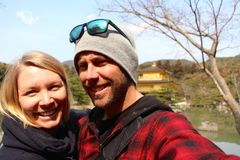 在金黄寺庙的年轻逗人喜爱的夫妇在京都 库存照片