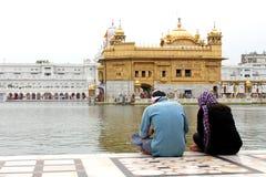 在金黄寺庙,阿姆利则,旁遮普邦,印度前面的夫妇 免版税库存图片