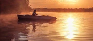 在金黄日落期间,一个年轻人在湖乘坐小船 剪影,日落的划船者的图象 荡桨在背后照明的人一条小船  库存照片
