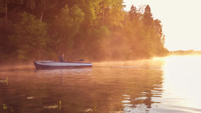 在金黄日落期间,一个年轻人在湖乘坐小船 日落的划船者 与自然概念的团结 免版税库存照片