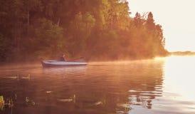 在金黄日落期间,一个年轻人在湖乘坐小船 日落的划船者 与自然概念的团结 图库摄影