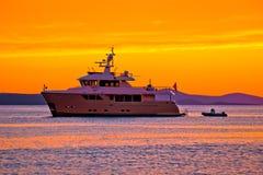 在金黄日落的游艇在公海 库存图片