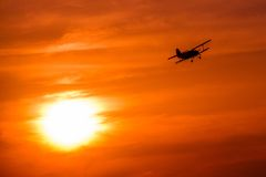 在金黄日落的飞机飞行 免版税库存照片