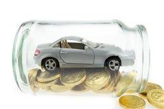 在金黄硬币的汽车模型在瓶子 库存图片
