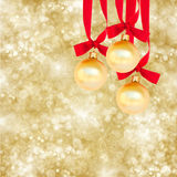 在金黄背景的三个圣诞节球 图库摄影