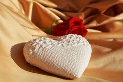 在金黄背景,关闭的心脏和红色玫瑰 免版税库存照片
