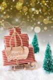 在金黄背景,文本圣诞快乐的垂直的雪橇 免版税库存照片