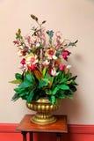 在金黄花瓶的塑料花的布置 库存图片