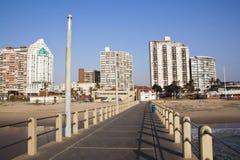 在金黄英里海滩前面的码头和城市地平线 免版税库存图片