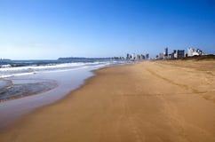 在金黄英里的空的海滩与德班市地平线 图库摄影
