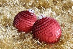 在金黄闪亮金属片的两个红色圣诞节中看不中用的物品 库存照片