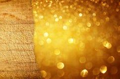 在金黄闪烁bokeh的残破的木纹理点燃 免版税库存图片