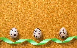 在金黄闪耀的背景的鹌鹑蛋 2个所有时段小鸡概念复活节彩蛋开花草被绘的被安置的年轻人 免版税库存照片