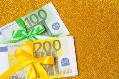 在金黄闪耀的背景的100张和200张欧洲票据 很多金钱,豪华 免版税库存照片