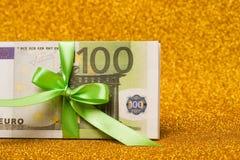 在金黄闪耀的背景的100张欧洲票据 很多金钱,豪华 库存照片