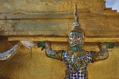 在金黄Chedi的巨人雕象在盛大宫殿复合体在曼谷,泰国 免版税库存图片