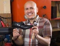 在针车床的工匠缝合的皮靴 免版税库存图片