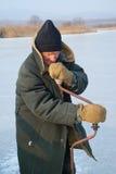 在钓鱼1的冬天的老人 库存照片