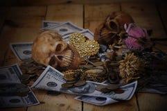 在钞票和硬币的头骨 库存图片