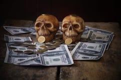 在钞票和硬币的头骨 免版税库存照片