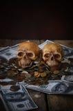 在钞票和硬币,金钱的头骨 图库摄影