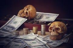 在钞票和硬币,金钱的头骨 库存图片