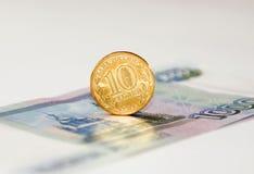 在钞票的一枚硬币 免版税库存照片
