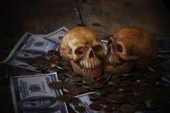 在钞票的头骨和硬币、金钱、概念在工作金钱的和死亡 库存照片