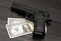 在钞票的黑枪 武装的刑事罪的概念 库存图片